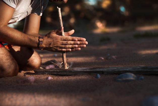 Człowiek próbuje podpalić starożytną metodą. piaszczysta plaża