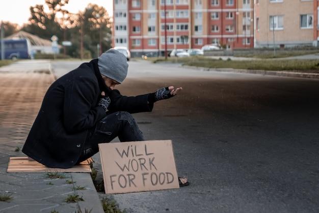Człowiek prosi o jałmużnę na ulicy ze znakiem będzie działać na jedzenie, bezdomnych