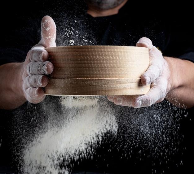 Człowiek przesiewa białą mąkę pszenną przez drewniane sito