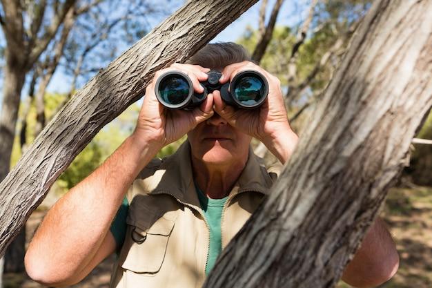 Człowiek przez drzewo patrząc przez lornetkę