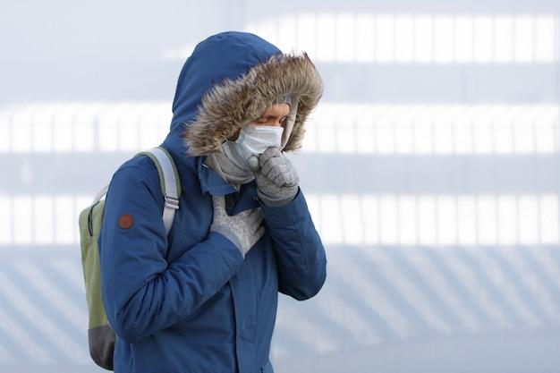 Człowiek przeziębiony, źle się czujący, kichający, kaszlący i noszący maskę medyczną