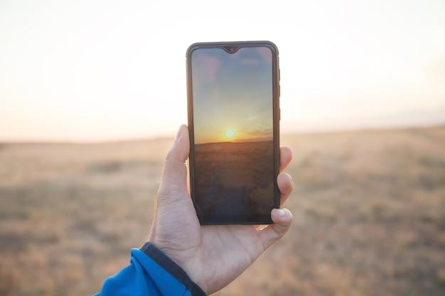 Człowiek przy zachodzie słońca ze swoim smartfonem.