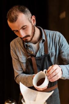 Człowiek przygotowuje kawę w ekspres do kawy