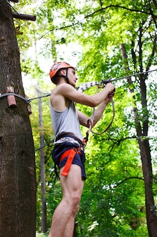 Człowiek przygotowuje się wspinać się na liny w parku