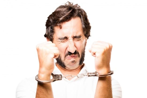Człowiek przykuty kajdankami policji