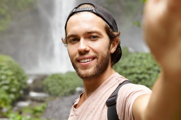 Człowiek, przyroda i turystyka. przystojny młody podróżnik w snapbacku uśmiecha się radośnie podczas robienia selfie, pozuje przy wspaniałym wodospadzie w lesie deszczowym
