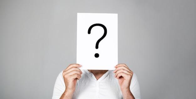 Człowiek pytanie. wątpliwy człowiek posiadający znak zapytania. problemy i rozwiązania. znak zapytania, symbol. zamyślony mężczyzna. uzyskiwanie odpowiedzi. portret mężczyzny, zaglądający za symbol przesłuchania. mężczyzna na białym tle