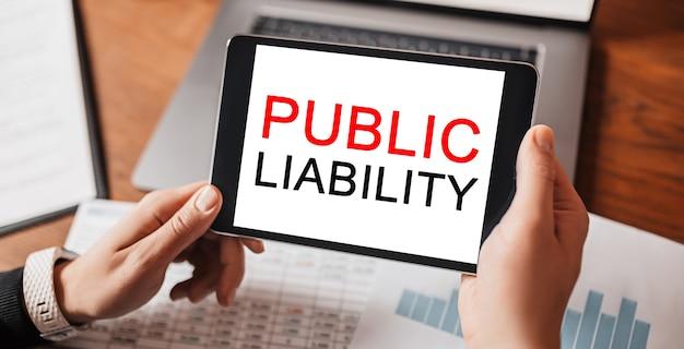 Człowiek ręce trzymając tablet z tekstem odpowiedzialność publiczna w miejscu pracy. biznesmen pracujący przy biurku z dokumentami