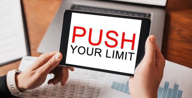 Człowiek ręce trzymając tablet z tekstem push limit w miejscu pracy. biznesmen pracujący przy biurku z dokumentami