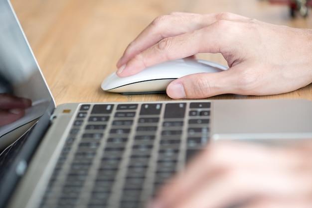Człowiek ręka na myszy za pomocą laptopa