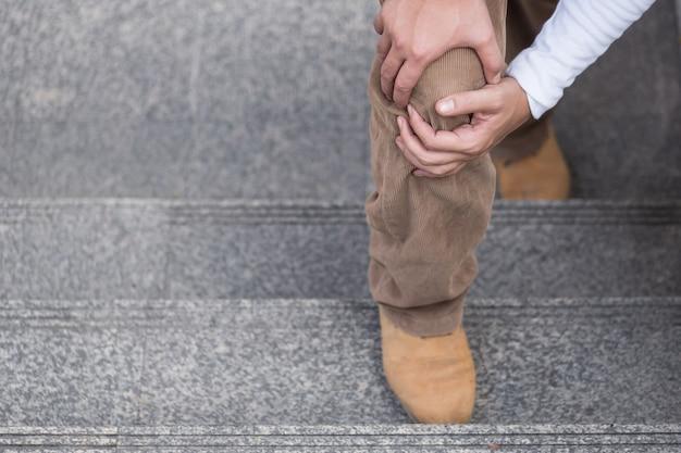 Człowiek ręka trzyma ból stawu kolanowego, nadmierne pojęcie przenoszenia masy
