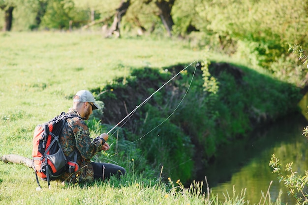 Człowiek relaksujący i łowienie ryb nad jeziorem. weekendy przeznaczone na wędkowanie. męskie hobby fisher. mistrz przynęt. zachowaj spokój i wędkuj. fishman szydełkowany wiruje do rzeki, czekając na duże ryby. facet wędkarski