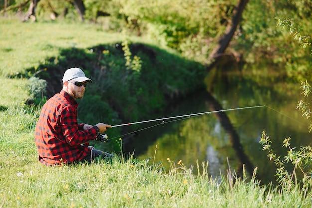Człowiek relaksujący i łowienie ryb nad jeziorem