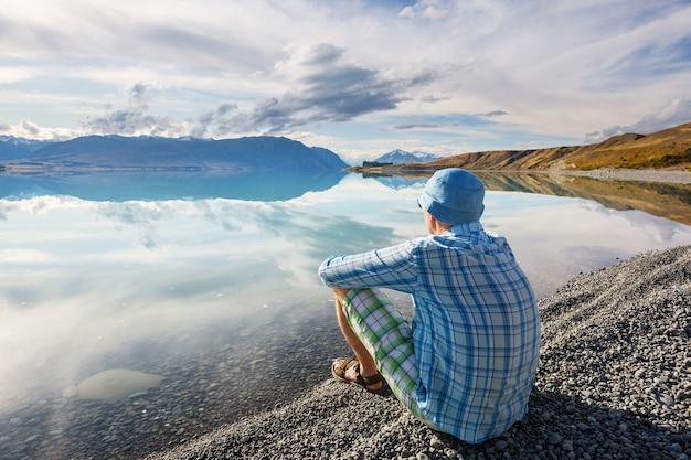 Człowiek relaksujący nad jeziorem piękne góry.