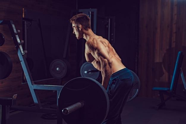 Człowiek robi ciężkie ćwiczenia na plecy. ból i zysk.