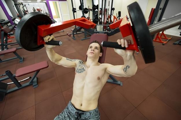Człowiek robi ćwiczenia klatki piersiowej na maszynie do wyciskania na ławce pionowej