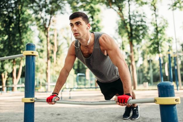Człowiek robi ćwiczenia pompek za pomocą poziomego paska