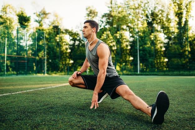 Człowiek robi ćwiczenia rozciągające na treningu na świeżym powietrzu