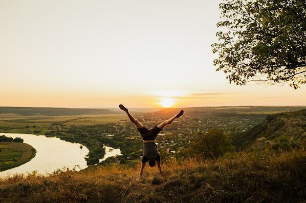 Człowiek robi handstand na trawie o zachodzie słońca niebo. młody sportowy człowiek robi ćwiczenia na rękach w pięknym górskim krajobrazie.