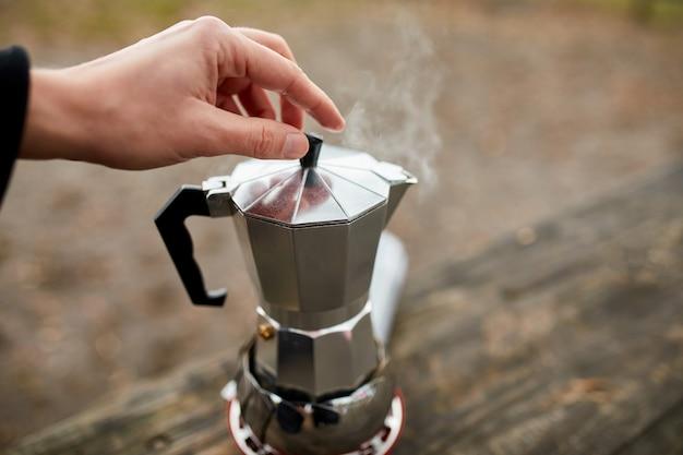 Człowiek robi kawę kempingową na świeżym powietrzu z metalowym gejzerem ekspres do kawy na palniku gazowym, krok po kroku.