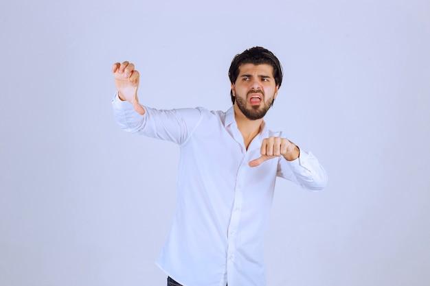 Człowiek robi kciuk w dół znak ręką.
