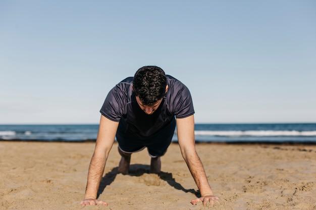 Człowiek robi push up na plaży
