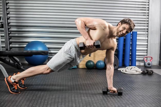 Człowiek robi push up z hantlami na siłowni crossfit