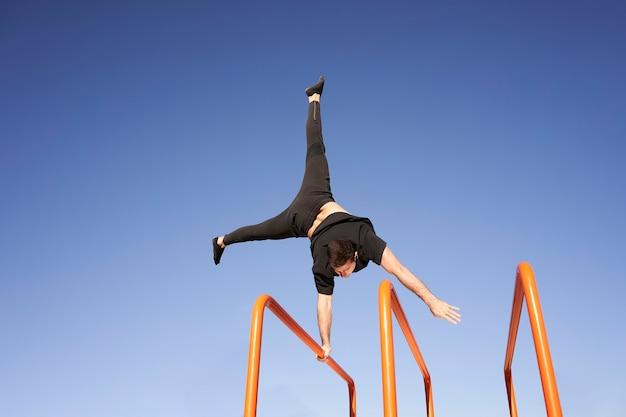 Człowiek robi równowagę jedną ręką, handstand na pasku. ćwiczenia na świeżym powietrzu. pojęcie zdrowego trybu życia, sportu, treningu, kalisteniki.