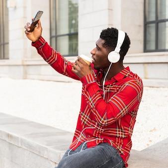 Człowiek robi selfie i słucha muzyki