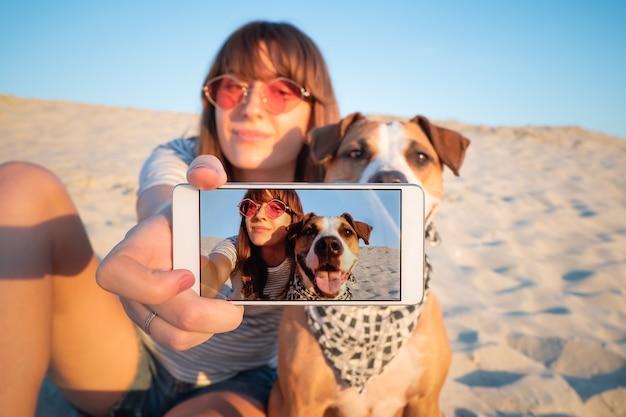 Człowiek robi selfie z psem. koncepcja najlepszych przyjaciół: młoda kobieta sprawia, że autoportret ze swoim szczeniakiem na zewnątrz na plaży