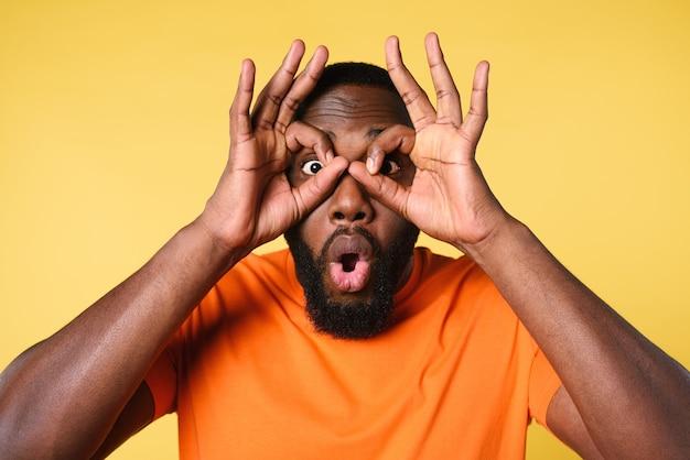 Człowiek robi szkło rękami. zdumiony i zszokowany wyraz twarzy. żółte tło