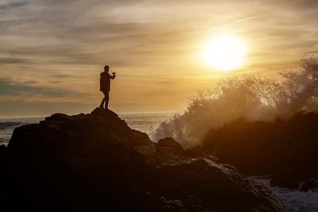Człowiek robi zdjęcia fal na klifie morskim smartfonem