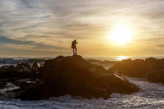 Człowiek robi zdjęcia fal na klifie przez smartfon o zachodzie słońca