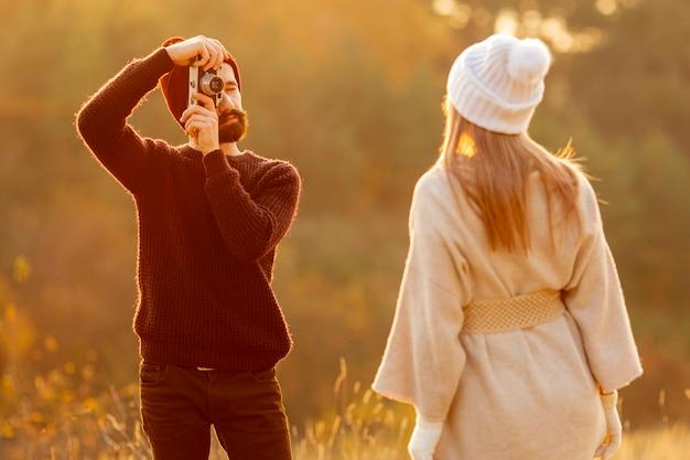 Człowiek robi zdjęcie swojego przyjaciela na zewnątrz