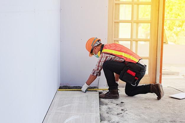 Człowiek robotnik z hełmem ochronnym budownictwo, budownictwo, nowy dom, koncepcje usług wewnętrznych budowy