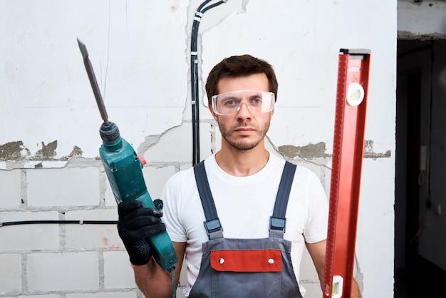 Człowiek robotnik z wiertarką udarową i poziom budynku na budowie
