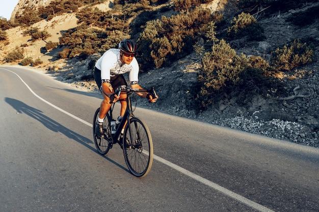 Człowiek rowerzysta pedałowania na rowerze szosowym na zewnątrz w słońcu na przybrzeżnej drodze