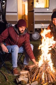 Człowiek rozpalający ognisko w zimną jesienną noc w górach. turyści z retro kamperem.