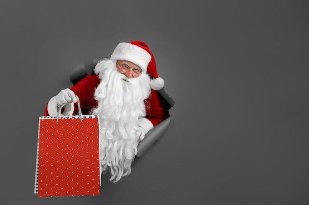 Człowiek santa trzyma w ręku pakiet sklepów przez otwór papieru. brodaty mężczyzna w santa hat patrząc przez dziurę na szarym papierze.