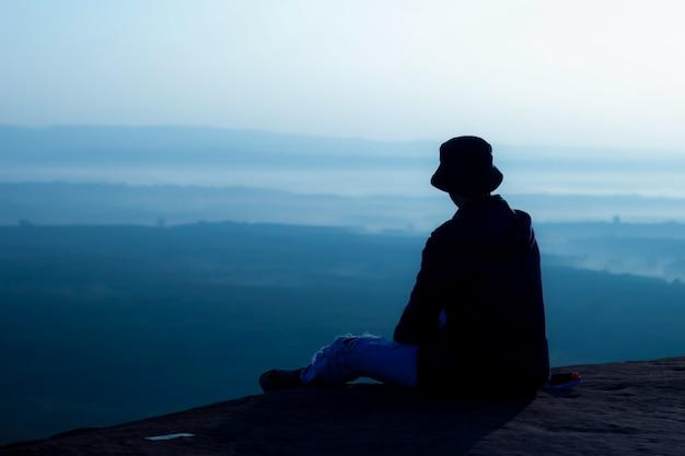 Człowiek siedzi i ogląda wschód słońca rano na klifie