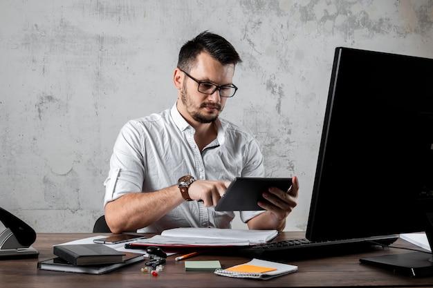 Człowiek siedzi przy stole w biurze, grając w telefonie. pojęcie pracy biurowej, lenistwo, zmęczenie. skopiuj miejsce.