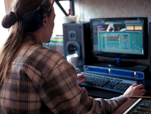 Człowiek siedzi w domu studio z profesjonalnym sprzętem muzycznym