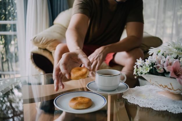 Człowiek sięga po ciasteczka i kawę.
