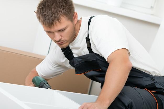 Człowiek składający meble do samodzielnego montażu w nowym domu. zrób to sam, nowa koncepcja domu i przeprowadzki