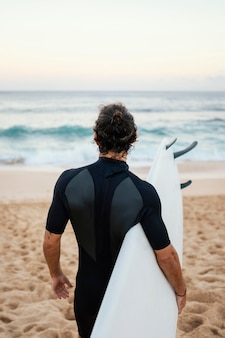 Człowiek sobie ubranie surfera, chodzenie po piasku