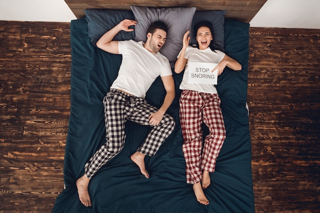 """Człowiek śpi i chrapie. kobieta trzyma """"stop chrapanie"""""""