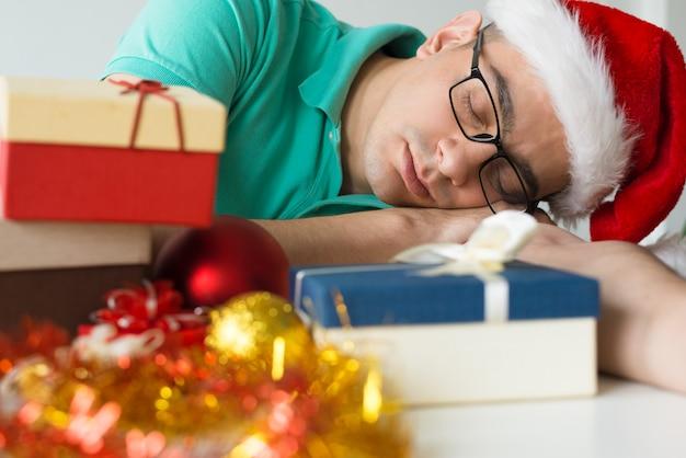 Człowiek śpi na stole z boże narodzenie prezenty i bombki