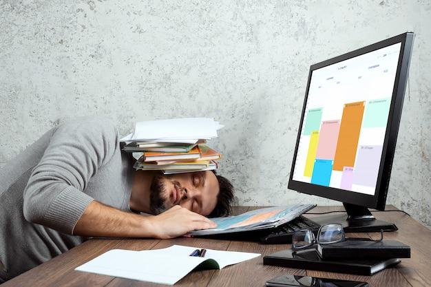 Człowiek śpi przy stole w biurze z dokumentami na głowie.