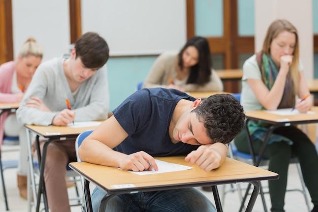 Człowiek śpi w sali egzaminacyjnej