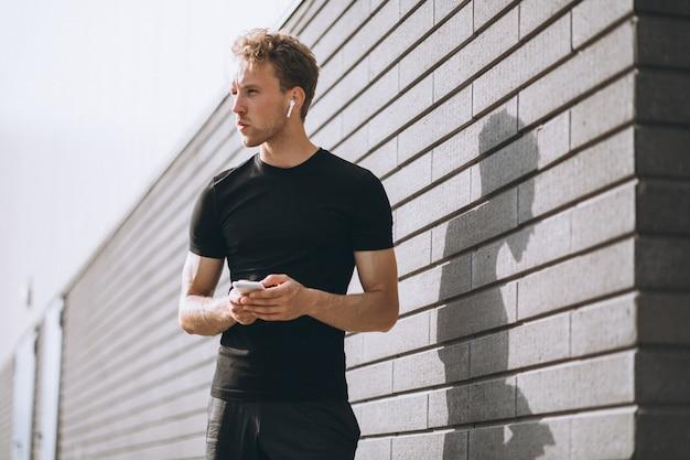 Człowiek sportowy jogging rano w mieście i przy użyciu telefonu